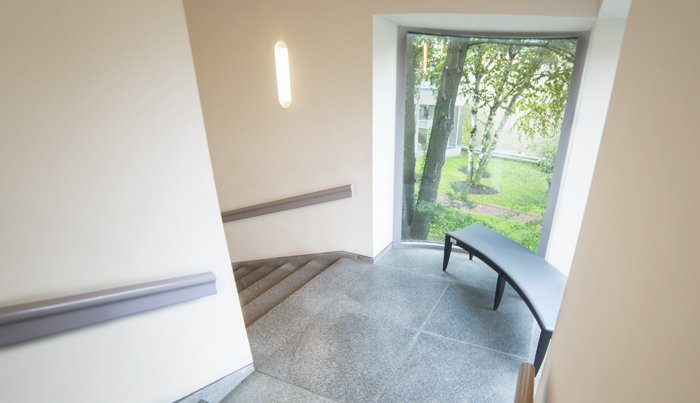 Photograph looking down a white-walled stairwell. Where the stairs turn to the left, there is a bench and a curved window looking over a garden below.