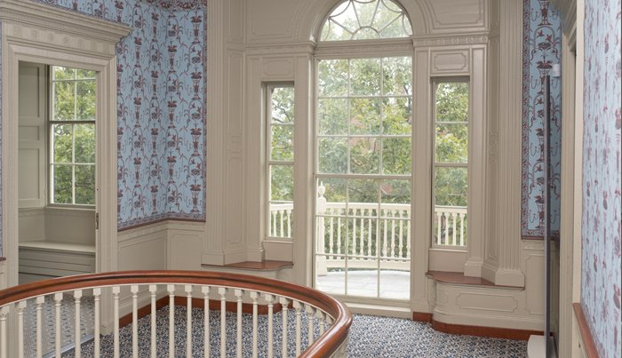 Photograph of an upstairs landing of a historic house with curved stair banister in the foreground and a large window beyond. The wallpaper and carpet are blue, with detailed but indistinguishable patterning.