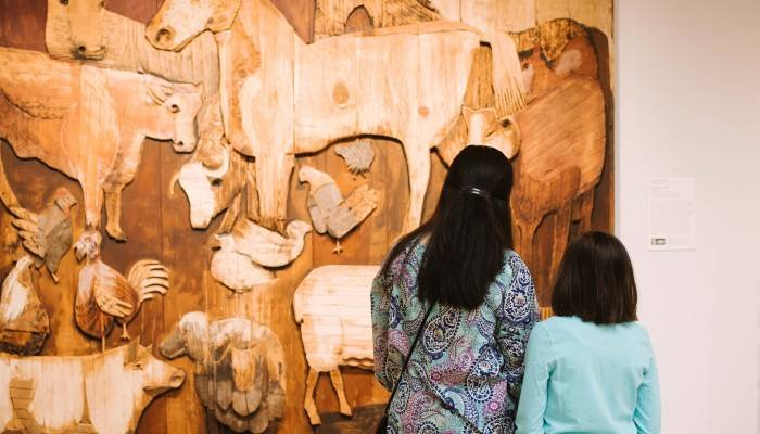 Two people, an adult and a child, stand with their backs to the camera looking at a carved wooden relief on the wall in front of them. The sculpture shows barnyard animals, carved from various types of wood in a variety of marks.