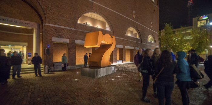 Museum exterior at night with Robert Indiana's Seven sculpture illuminated and crowds of people in winter clothes scattered throughout.